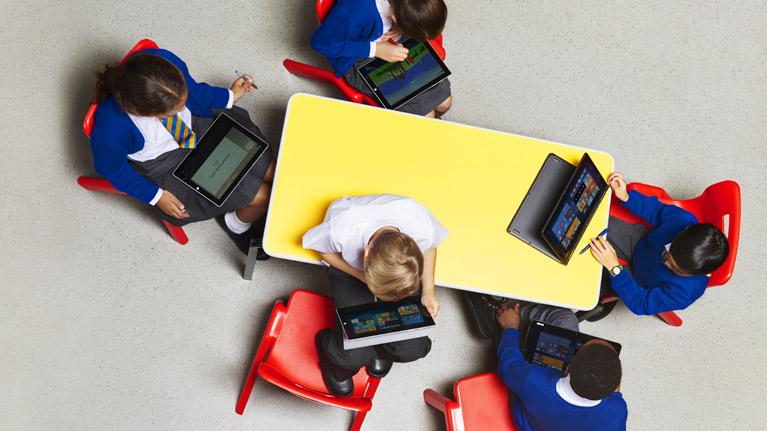 Estudiantes que trabajan en el aula con dispositivos Windows.