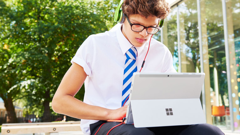 A photograph of a student wearing headphones and working on a Microsoft Surface.