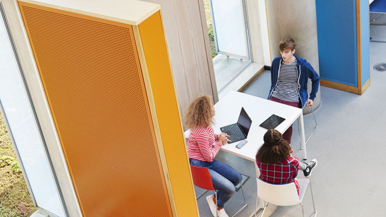 A photograph shot from above of three students working in an education institution.