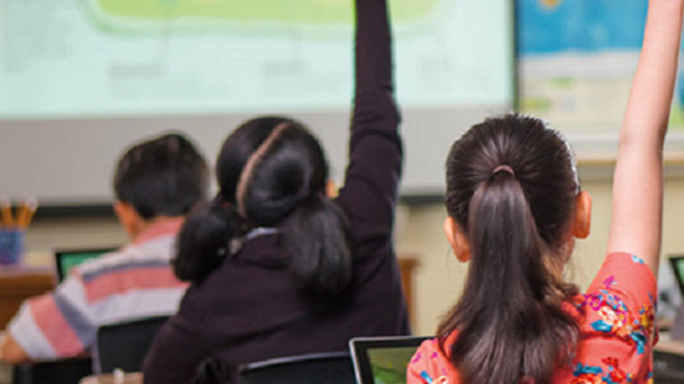 質問に答える小学生クラスで手を彼等の物を上げる女子校生のイメージ。...........................................