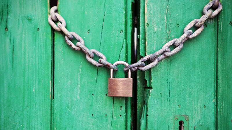 Image of a large green wooden door with a padlock and chain.