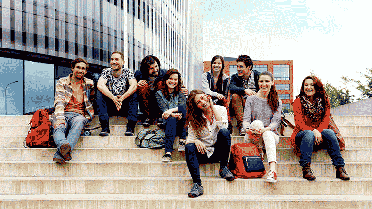 University students sitting outside on steps posing for the image.