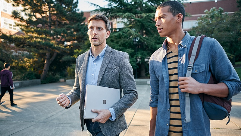 An educator and student walking outdoors with a Microsoft Surface.