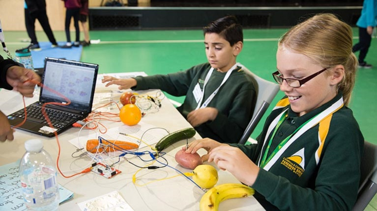 Students working with fruits and electricity in a science classroom.