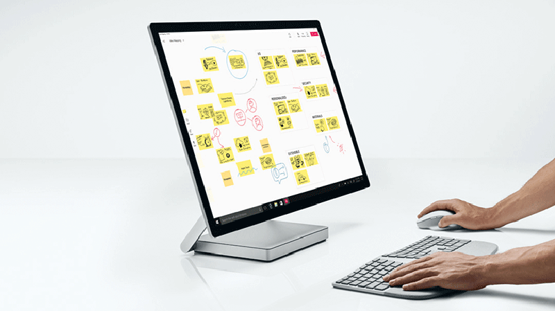 Image of a user using a desktop computer, the screen displays miscellaneous planning notes