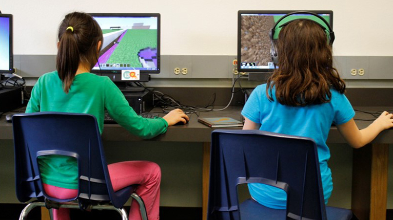 dva studenti používající Minecraft: Education Edition na stolních počítačích