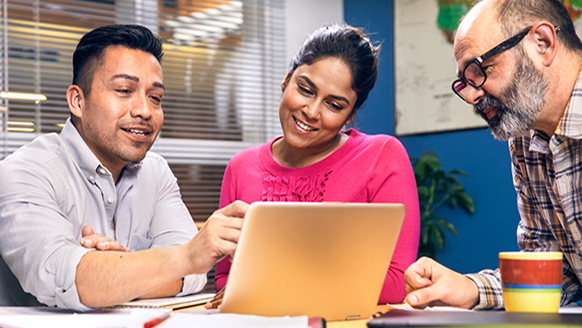 Educadores que olham o dispositivo com Microsoft Forms