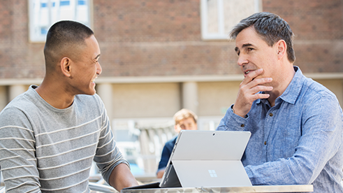 This is an image of two men having a conversation while using a microsoft surface