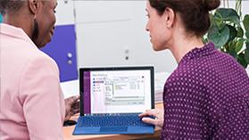 Dois educadores usando o OneNote para criar notebooks digitais em sala de aula