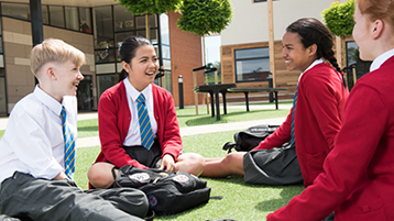 this is an image of four older school pupils talking in a outdoor common area within a school