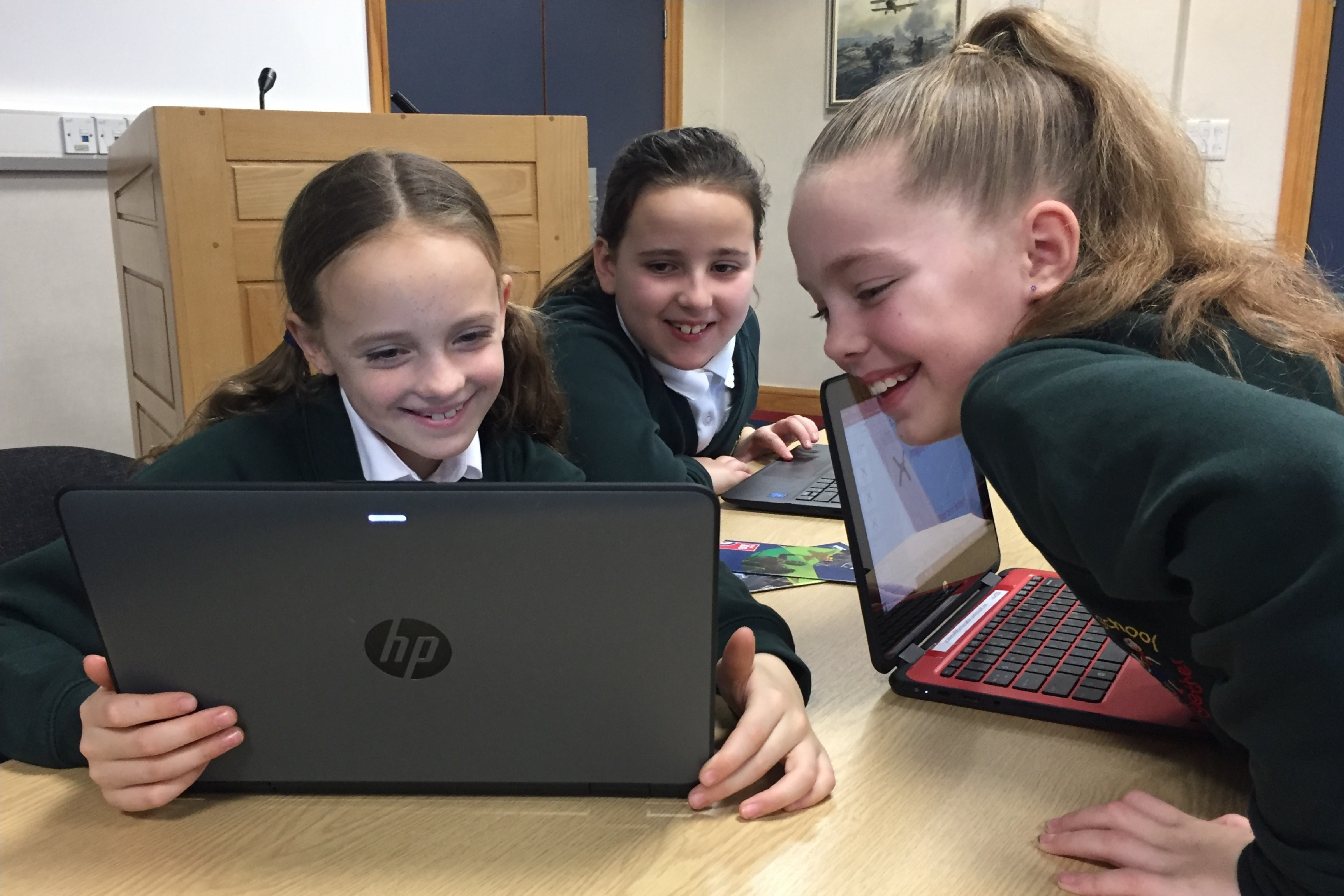 A photograph of three school children completing work on a HP device