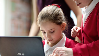 Two pupils look at a laptop - Making schools outstanding