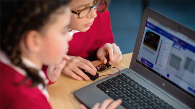 Two pupils looking at laptop - Tools that make teamwork better