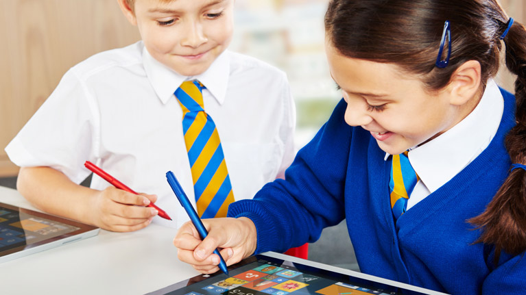 Two students working in the classroom with tablets and digital pens.