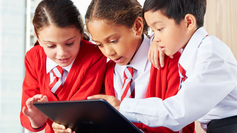 Three students working together on a tablet in school.