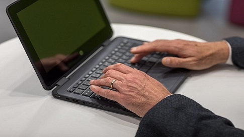 an image of hands rested on a laptop keyboard is shown here.