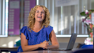 Lady with computer smiling at camera - Become a Microsoft Innovative Educator