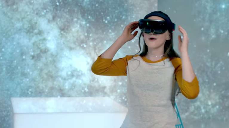 Woman wearing HoloLens glasses in the middle of a galaxy setting.