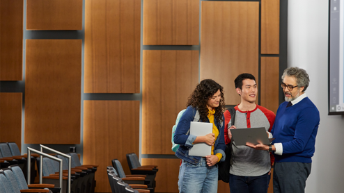 two students discussing with teacher in an auditorium while holding a laptop