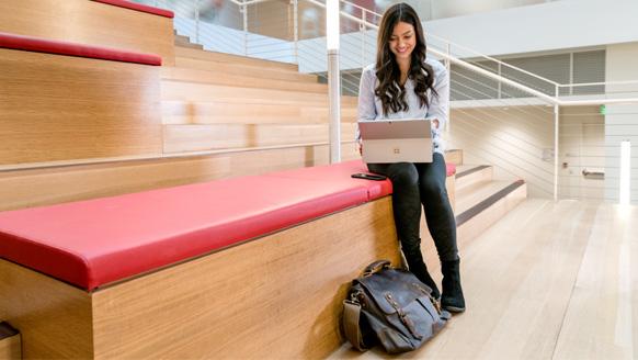 Studentin, die auf Treppen im Universitätsgebäude sitzt und Surface Pro verwendet (Bildschirm nicht gezeigt). Neben ihr sitzt ein Telefon und eine Laptoptasche.