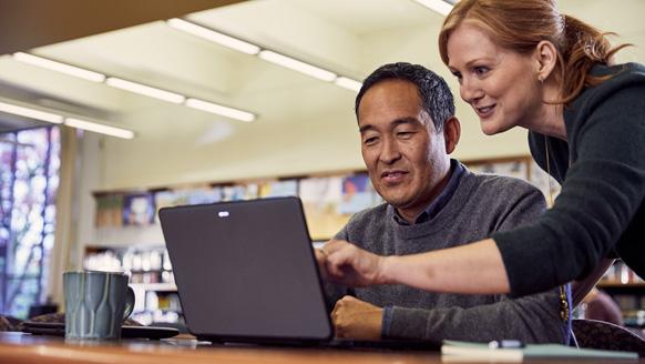 Lehrerin, die einen Lehrer in einer Bibliothek anweist. Sie schauen gemeinsam auf einen Laptop.