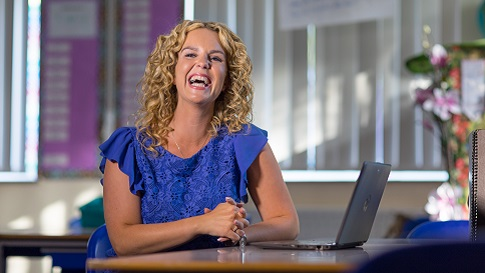 this is an image of a women with blonde hair smiling, while sitting next to a laptop