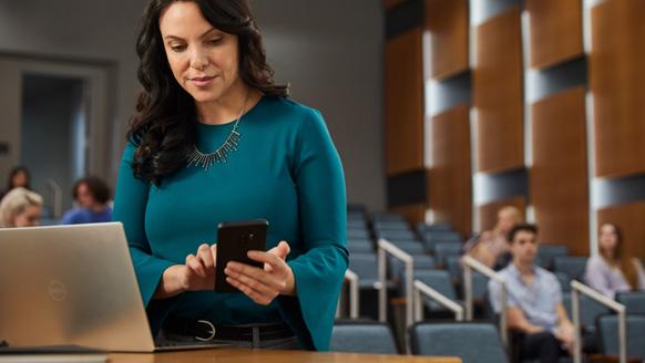 Hochschulbildung. Dell XPS 13. Eine Lehrerin in einem Hörsaal, die eine mehrstufige Authentifizierung durchführt, um auf Kursmaterialien zuzugreifen, während die Studenten auf den Unterricht warten.