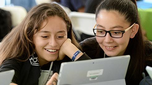 ラップトップを使用して2つの若い女の子のイメージはここに示されている     .