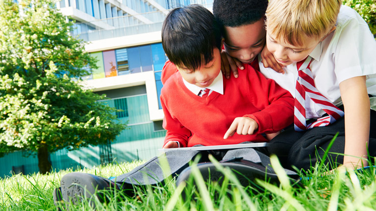 Three primary students working together on a tablet.