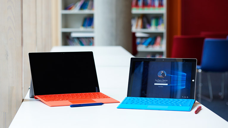 A photograph of two Microsoft Surface devices opened on a table.